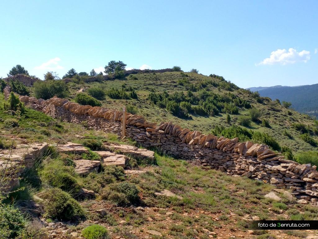 La senda de la Talaya crestea la loma junto a los muros de piedra